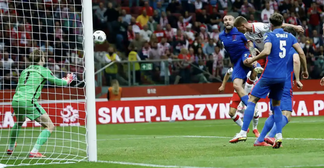 Poland's  substitute  Damian Szymanski who rises high above Luke Shaw to power home his first goal for his country and equalises.